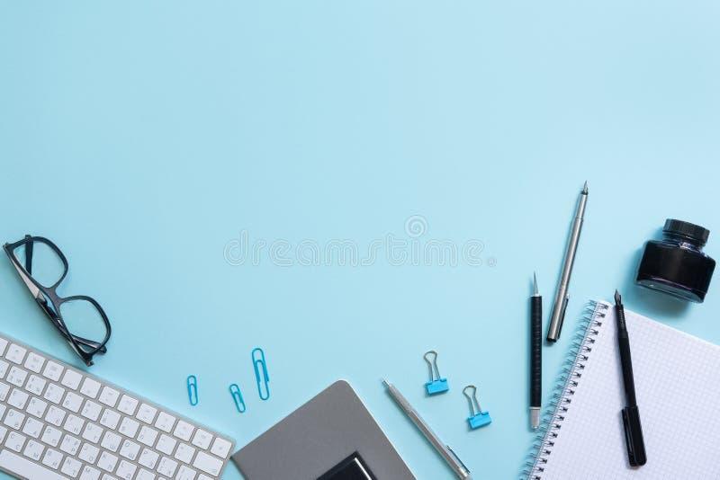 Blå tabell för kontorsskrivbord med den tomma anteckningsboken, datortangentbordet och andra kontorstillförsel royaltyfri fotografi