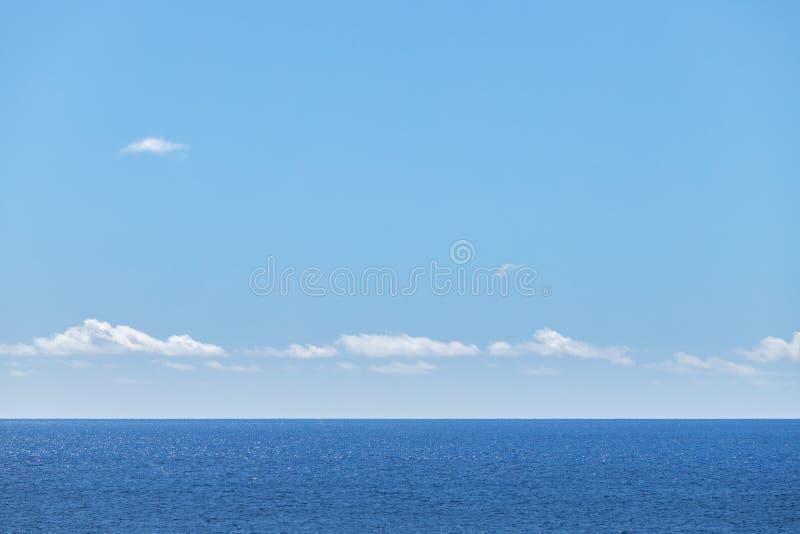Blå tangent med moln och blått hav royaltyfria bilder