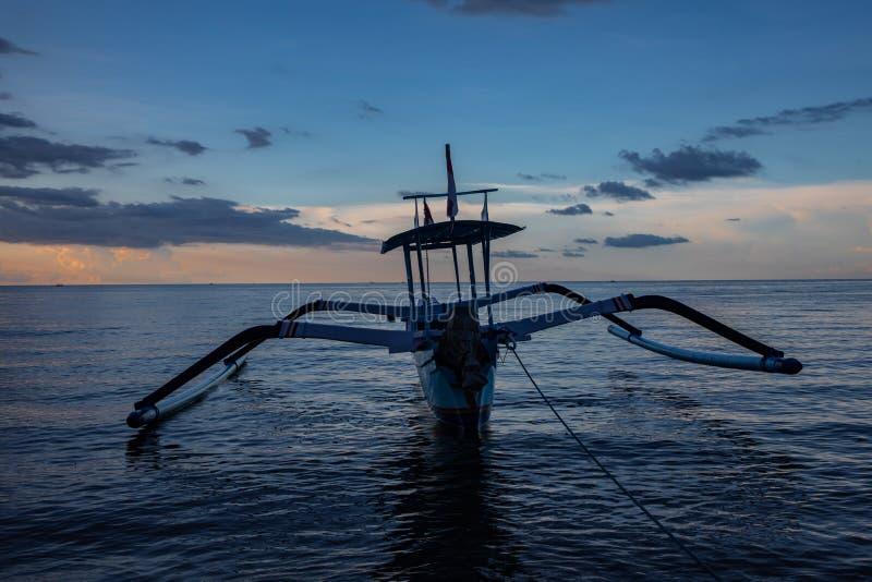 Blå timme över det lugna havet och den svarta sandstranden med balinesefartyget royaltyfri fotografi