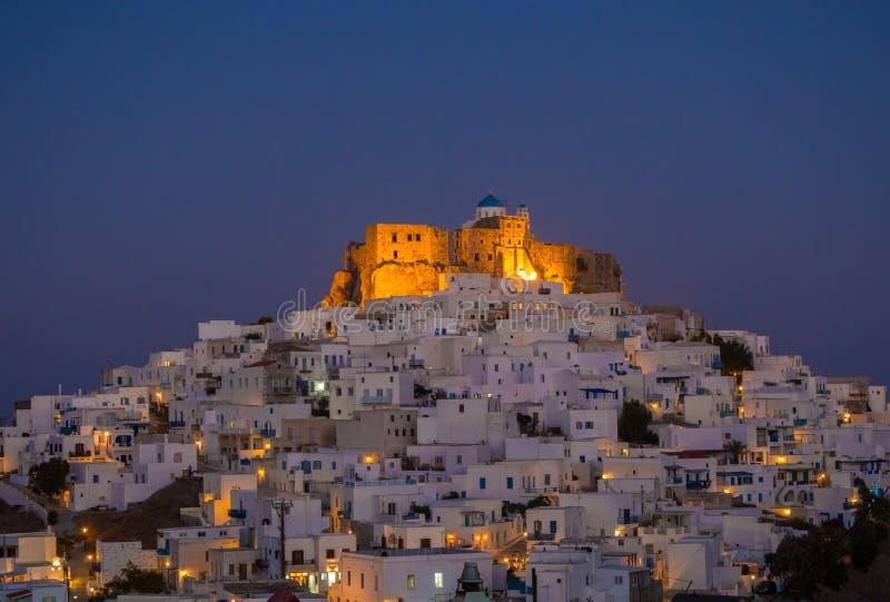 Blå timme i Astypalaia, Grekland med ljusen som startar att visa royaltyfri bild