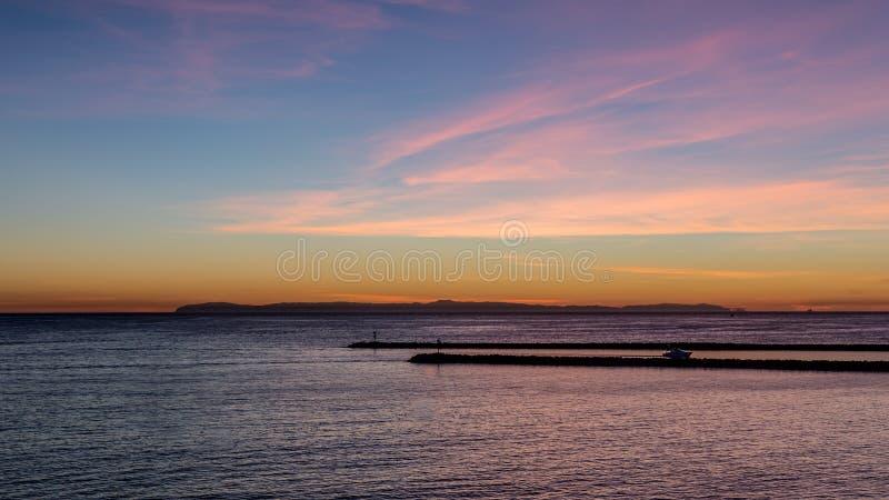Blå timmesolnedgång med ljusmoln och rosa och orange toner över Stilla havet i det orange länet, Kalifornien royaltyfria foton