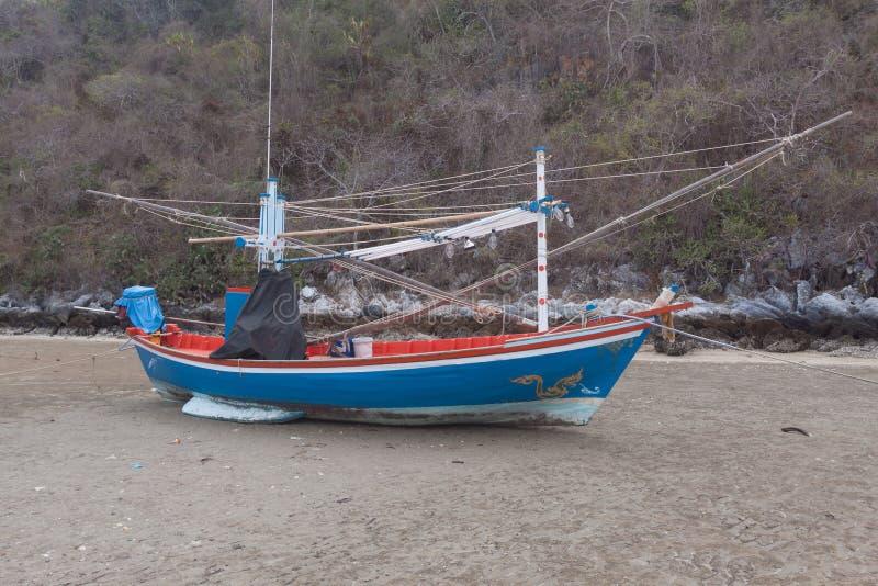 Blå träfiskebåt på lågvattenstranden arkivbild