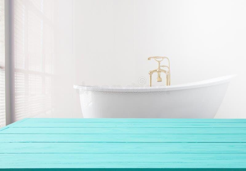 Blå trähylla på badrumbakgrund Träskrivbordtabell med utrymme för bästa sikt och kopieringsnära det vita badet på hotellet f?r re royaltyfri bild