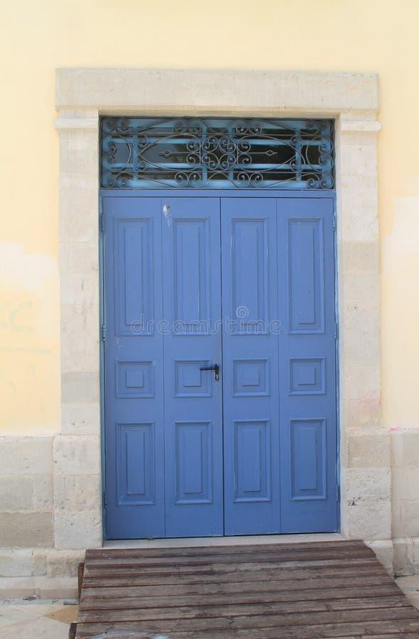 Blå träytterdörr med galler royaltyfri foto
