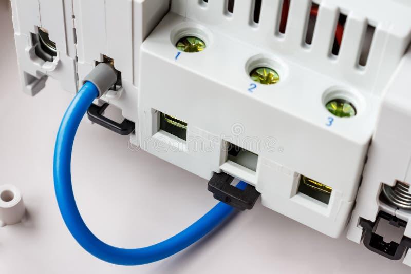 Blå tråd förbindelse till den automatiska closeupen för strömkretssäkerhetsbrytareport fotografering för bildbyråer
