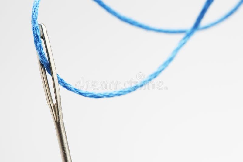 Blå tråd som går till och med visarögonnärbild arkivbild