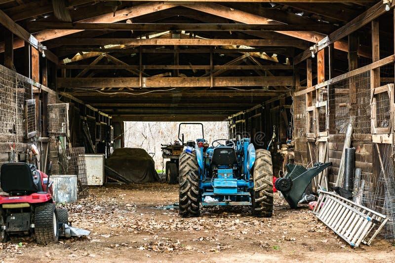 Blå traktor i ett stall royaltyfri foto