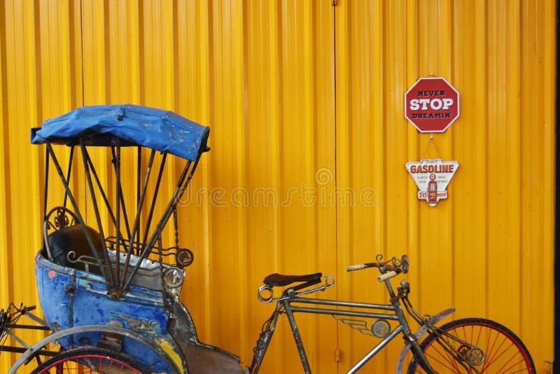 Blå trehjuling med gul bakgrund royaltyfria bilder