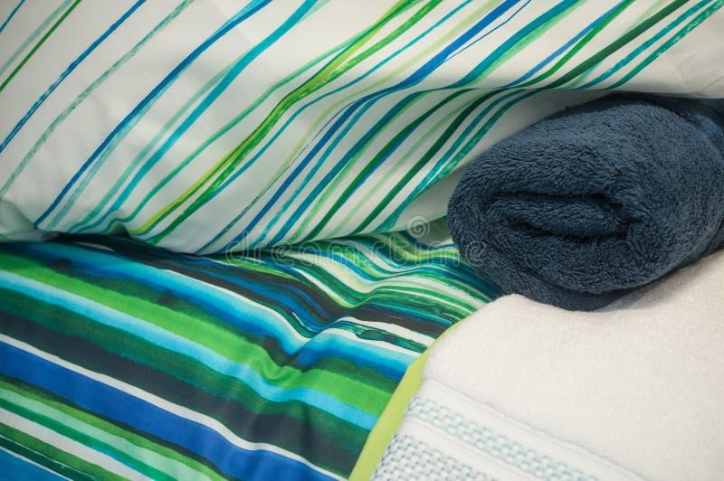 blå uppsättning av sänglinne och den rullande badlakanet i lager royaltyfri bild