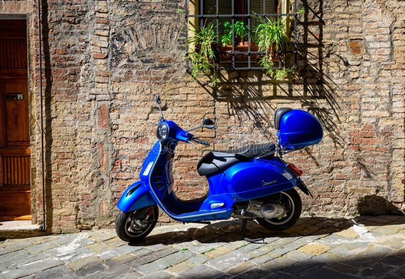 Blå Vespasparkcykel som parkeras på den gamla gatan i Siena, Italien royaltyfri bild