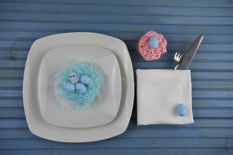 Blå vit för inbrott för påskschemaställe och dekorerat med pappers- en redeeaster ägg och en rosa hemlagad muffin royaltyfria foton