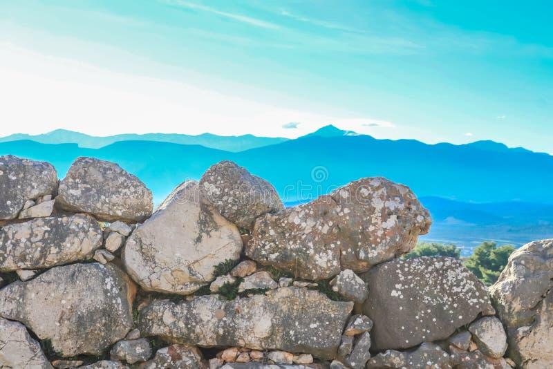 Blåa berg i det beskådade avståndet från vaggaväggarna av det forntida kullefortet av Mycenae nämnde i HomersIliad royaltyfri bild