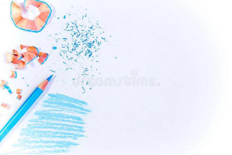 Blåa blyertspenna och shavings på en vit bakgrund arkivbilder