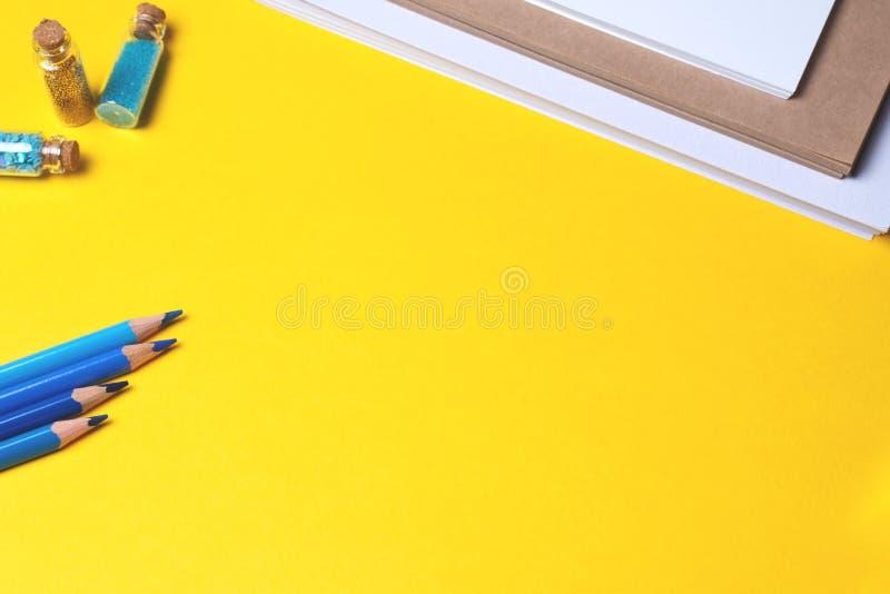 Blåa blyertspennor på gul bakgrund med notepaden och flaskor arkivbild