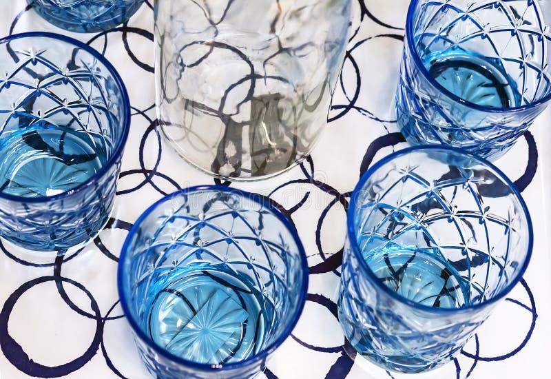 Blåa exponeringsglasbägare med den vita karaffen Kitchenware från blått exponeringsglas royaltyfri fotografi