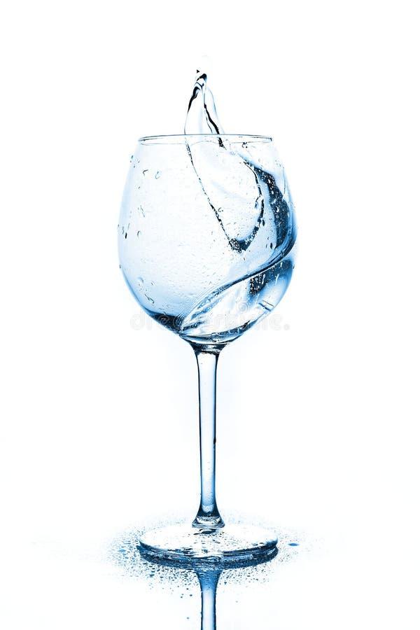 Blåa färgstänk av rent vatten i vinexponeringsglaset en sprej av vatten dricksvatten arkivfoto