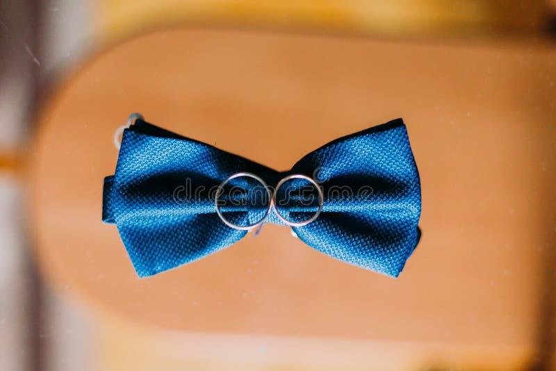 Blåa fluga och vigselringar på träbakgrund arkivfoto