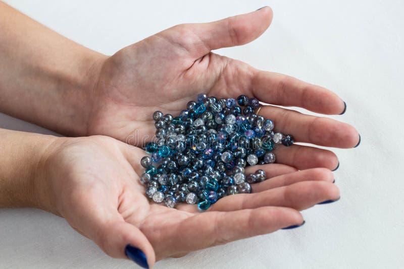 Blåa glass pärlor på kvinnahänder royaltyfria bilder