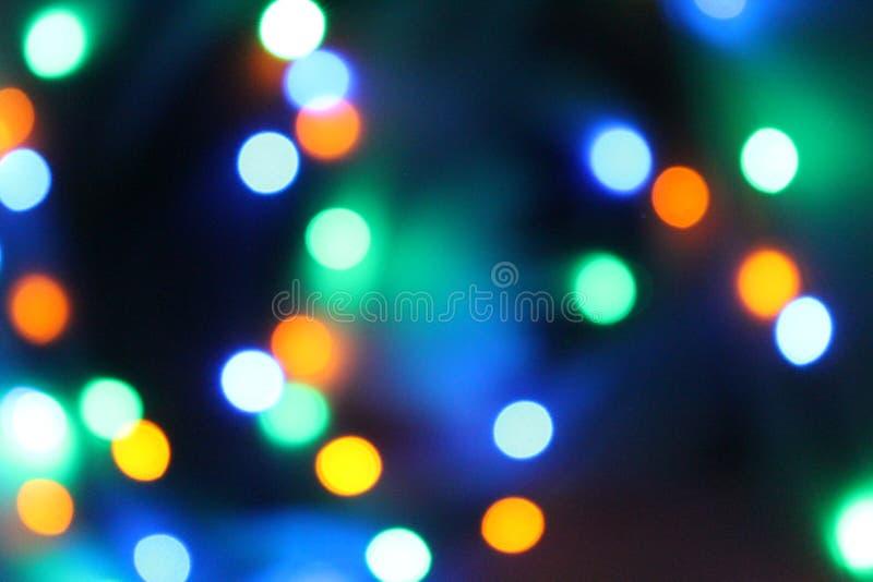Blåa, gula, gröna och vita signaler för abstrakt ljusbokeh på svart bakgrund arkivfoto
