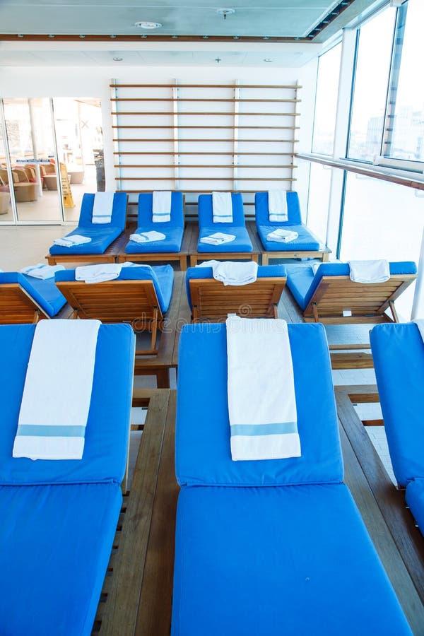 Blåa handdukar på blåa Chaise Lounges arkivfoto