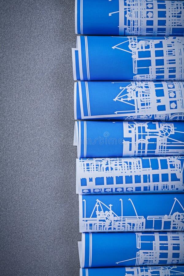 Blåa hoprullade byggnadsritningar på bästa sikt för grå bakgrund fotografering för bildbyråer