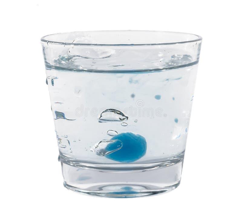 Blåa iskuber som plaskar in i exponeringsglas av vatten arkivfoton