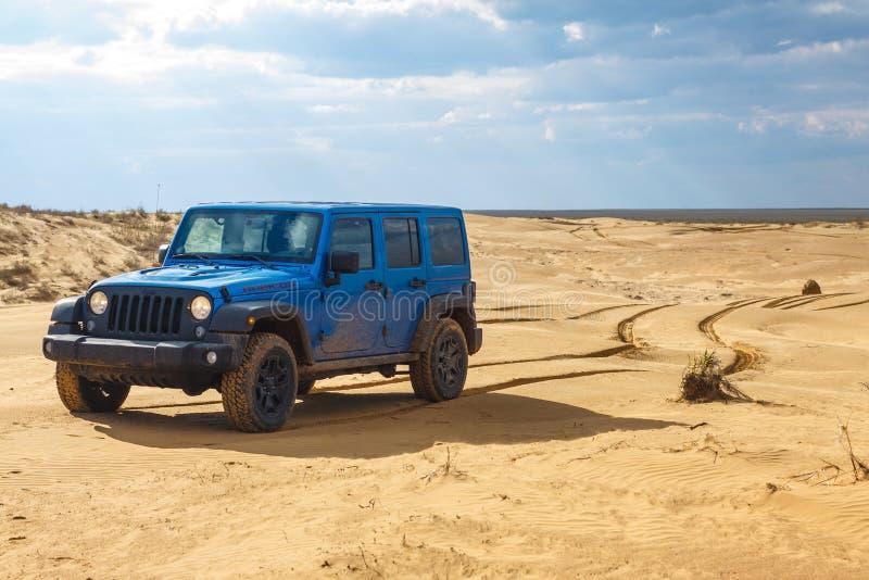 Blåa Jeep Wrangler Rubicon Unlimited på ökensanddyn arkivbild