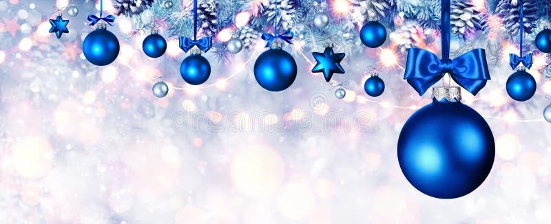 Blåa julbollar som hänger på granfilialer arkivbild