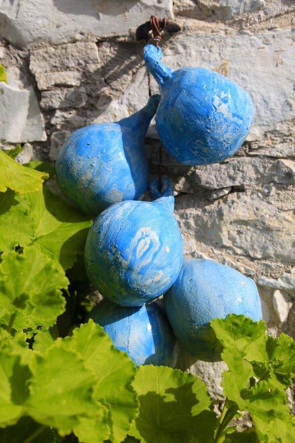 Blåa keramiska tillbringare på en bakgrund av den gamla stenväggen i by, arkivfoton