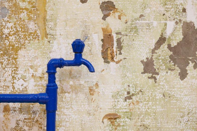 Blåa klapp och rör på grungeväggen arkivbild