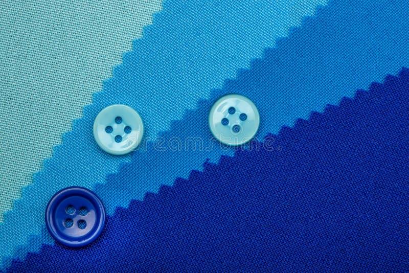 Blåa knapp och prövkopior av tygtexturdetaljen fotografering för bildbyråer