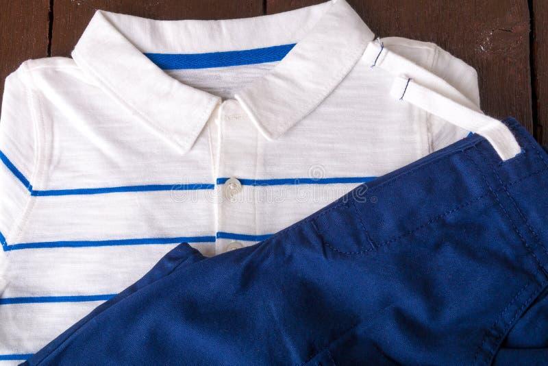 Blåa kortslutningar och vit randig polo på brun träbakgrund Pojkedräkt Top beskådar royaltyfri foto