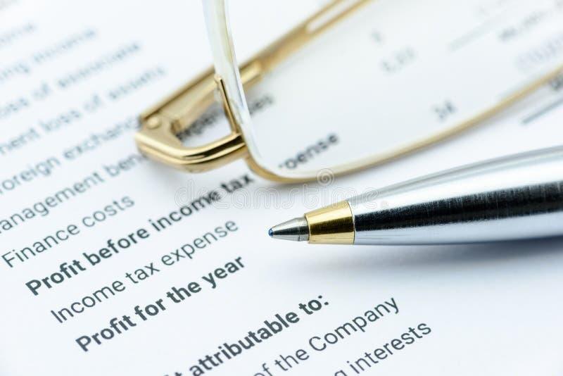 Blåa kulspetspenna- och ögongräs på ett företags finansiella rapport, i delen av vinst och nettoinkomst royaltyfri foto