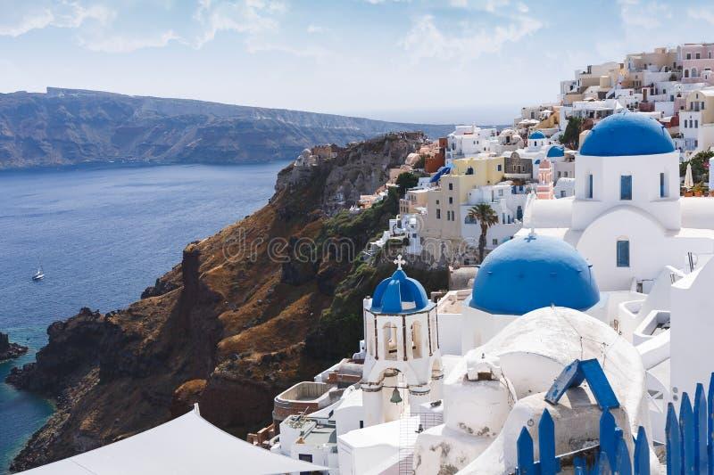 Blåa kupoler och att sätta en klocka på tornet av kyrkor i Oia, Santorini, Grekland royaltyfri bild