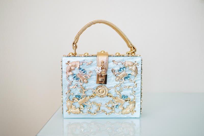 Blåa kvinnors handväska med det guld- handtaget arkivfoton