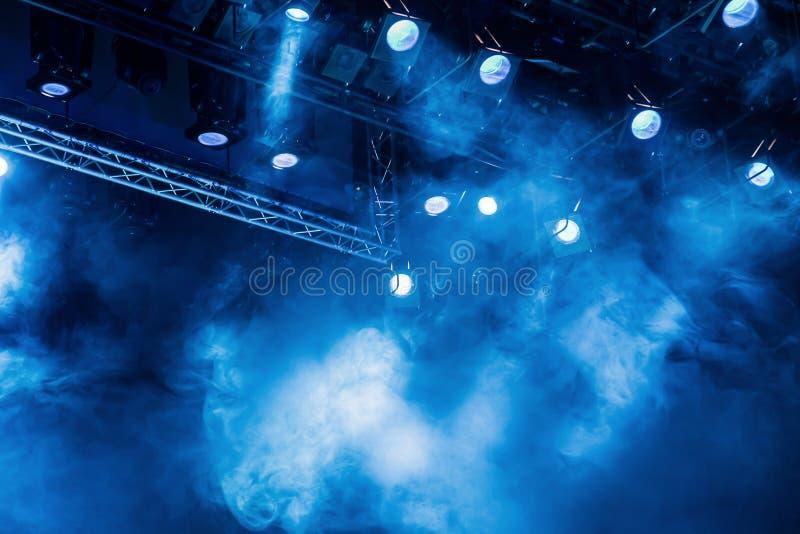 Blåa ljusa strålar från strålkastaren till och med röken på teatern eller konserthallen Belysningsutrustning för en kapacitet ell royaltyfri foto