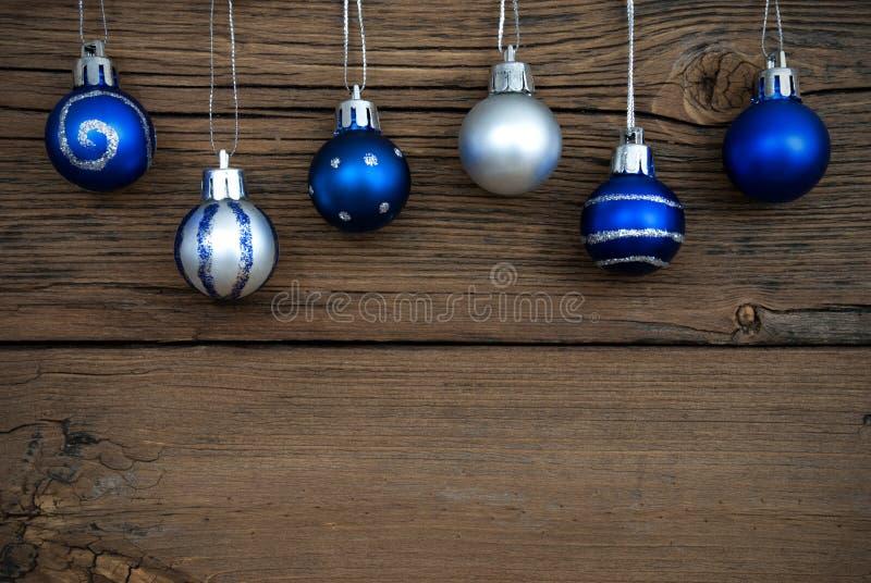 Blåa och silverjulgranbollar på trä royaltyfria bilder