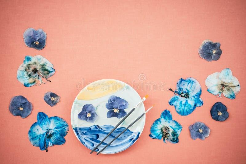 Bl?a pansies och m?lad keramisk platta royaltyfri bild