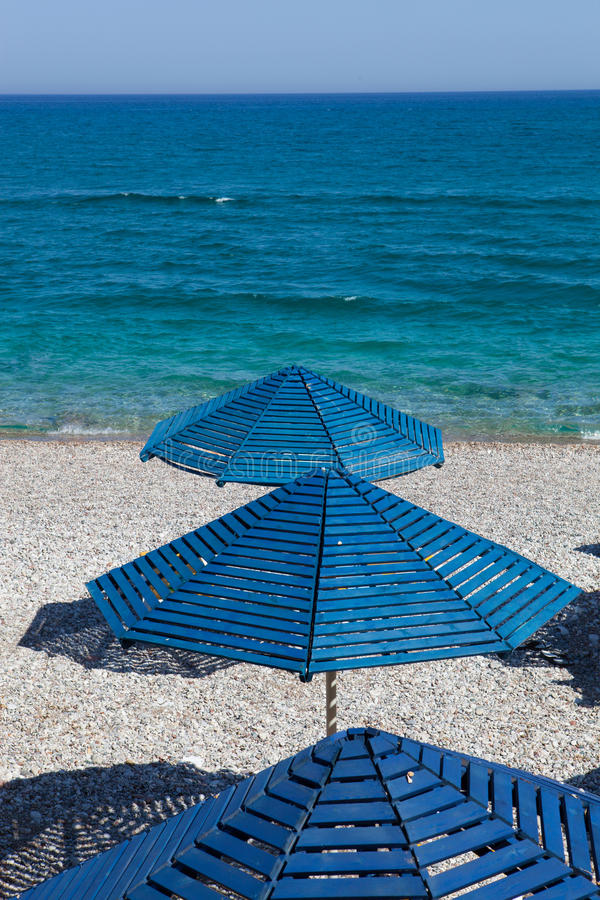 Blåa paraplyer på en strand royaltyfria foton