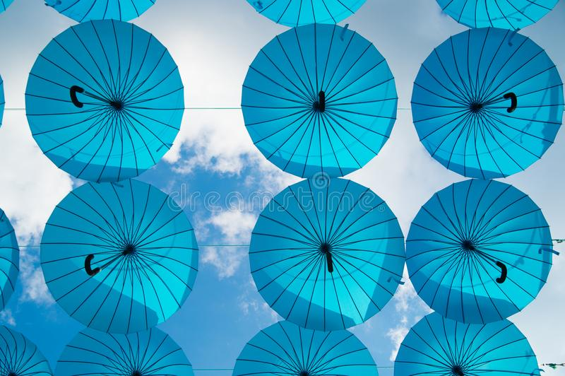 Blåa paraplyer svävar i himmel på solig dag Installation för paraplyhimmelprojekt Ferie- och festivalberöm Skugga och arkivbilder