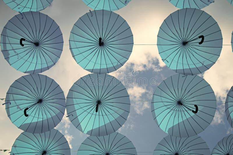 Blåa paraplyer svävar i himmel på solig dag Installation för paraplyhimmelprojekt Ferie- och festivalberöm Skugga och royaltyfria bilder