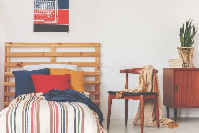 Blåa, röda och orange kuddar på enkel säng med det avrivna duntäcket och trähuvudgaveln i oldschoolsovruminre, verkligt foto arkivfoto