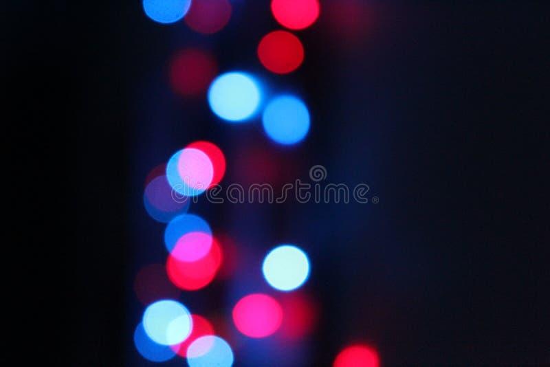 Blåa, röda, rosa och vita signaler för abstrakt ljusbokeh på svart bakgrund arkivbilder