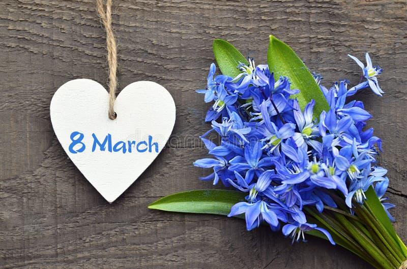 Blåa Scilla blommar och dekorativ trähjärta på gammal träbakgrund för 8 för kvinna` s för mars internationell dag arkivfoto