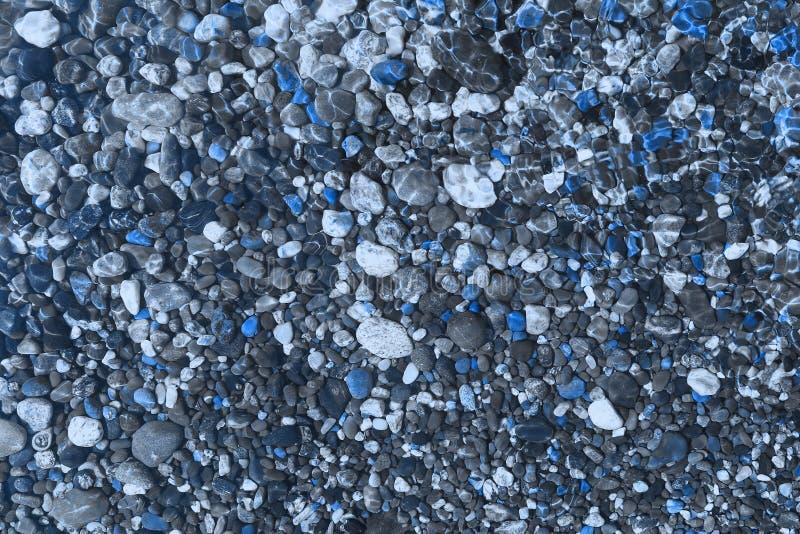 Blåa skinande havstenar som är våta vid vågtextur - trevlig abstrakt fotobakgrund royaltyfri foto