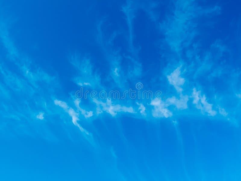 Blåa skys och ormbunke formade moln som är ljusa och whispy vid na royaltyfri foto