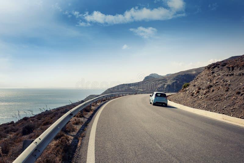 Blåa små bilritter längs en slingrande bergväg längs fotografering för bildbyråer