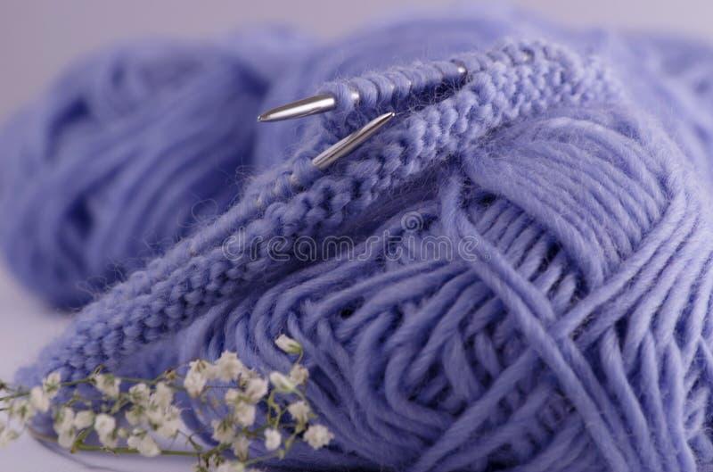 Blåa sticka trådar, stickor och stack öglor ligger på tabellen Sticka textur Blur verkställer royaltyfri bild