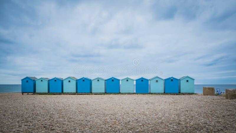 Blåa strandhus på stranden nära Charmouth i Dorset, UK royaltyfri bild