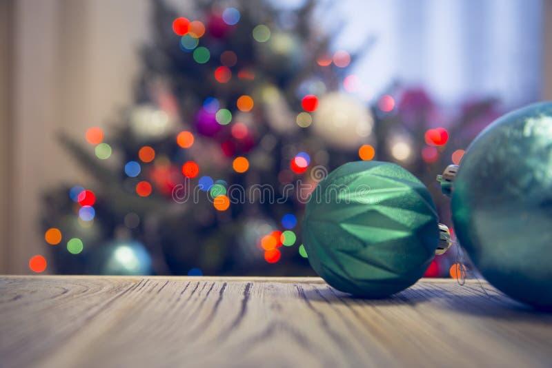 Blåa struntsaker på en trätabell mot den dekorerade julgranen arkivbild